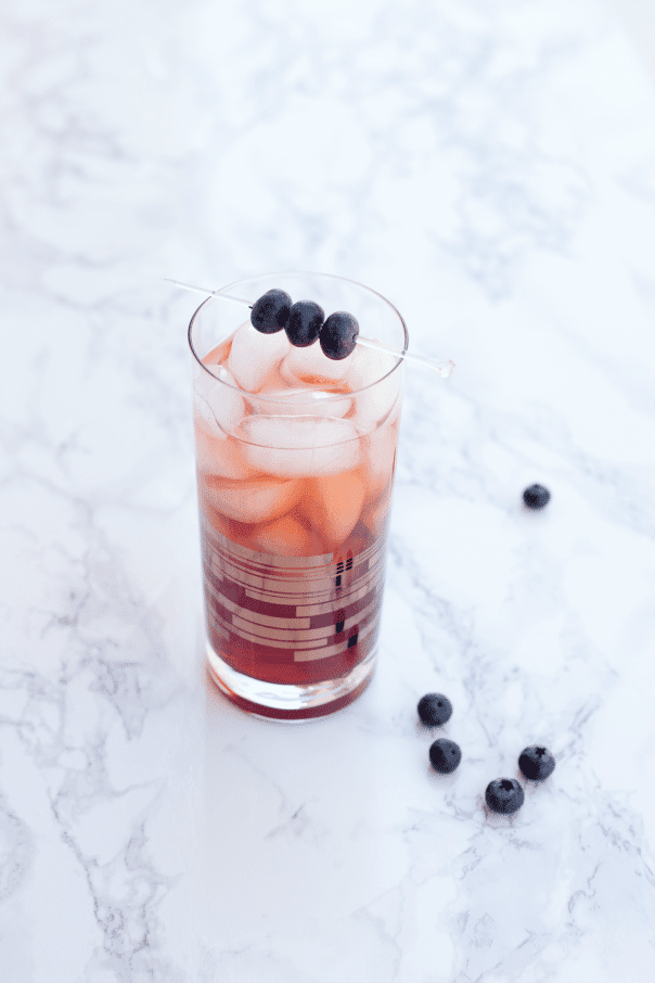 glass of blueberry tea on white marble counter