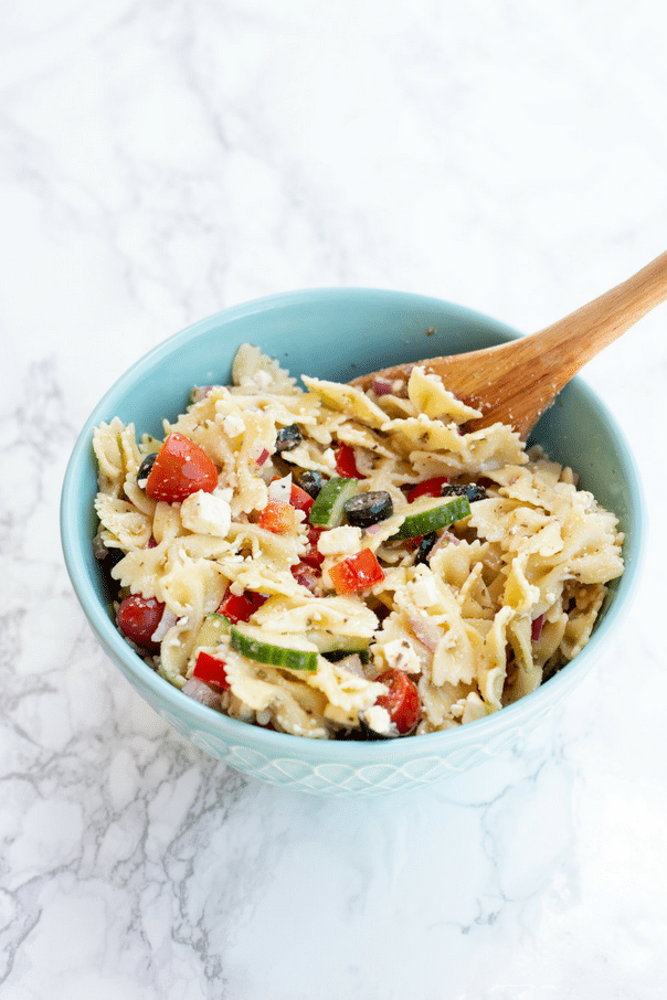 Greek pasta salad with tomatoes, and cucumbers in blue bowl