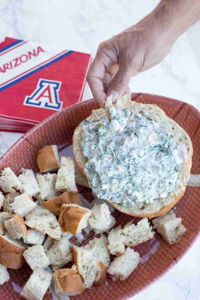 Hand dipping bread into spinach ham dip (spinach dip)